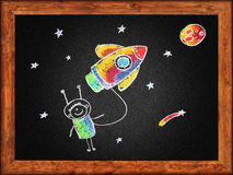 Happy boy with rocket. Black blackboard with frame and kids drawing. Color chalks royalty free illustration