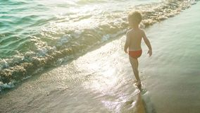 Happy boy run and jump merrily and splashing in the sea water in sunset. Slowmo stock video