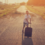 The  happy boy run with a suitcase in a summer Royalty Free Stock Photo