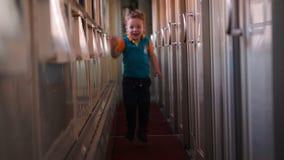 Happy boy running along the train hallway. Happy little boy running along the train hallway stock video