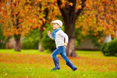 Happy boy running in autumn park Stock Photography