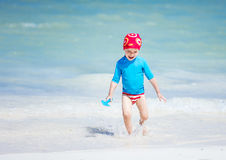 Happy boy running in breaking waves on the beach Stock Photos