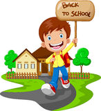Happy boy running while carrying a sign that read back to school Royalty Free Stock Image