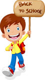 Happy boy running while carrying a sign that read back to school Stock Photography