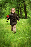 Happy boy running on grass Stock Photography