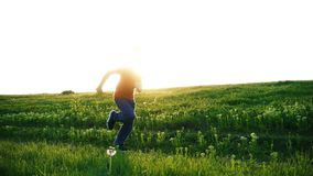 Happy boy running on green grass meadow stock footage