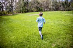 Happy boy running outside. A back view of an active five year old boy running in a yard royalty free stock image