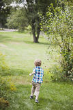 Happy boy running outside. A back view of  an active toddler boy running in a yard Royalty Free Stock Images