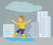 Happy boy running through puddles in the city Stock Photo