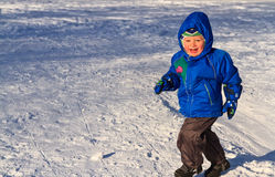 Happy boy running in snow Stock Photo