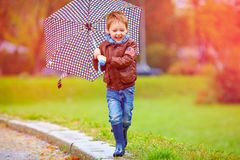 Happy boy running under an autumn rain Stock Image