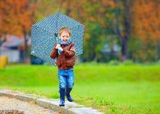 Happy boy running under an autumn rain Stock Image