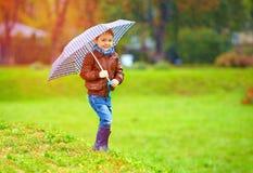 Happy boy running under an autumn rain Royalty Free Stock Photography