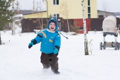 Happy boy running at a winter cottage village royalty free stock photos