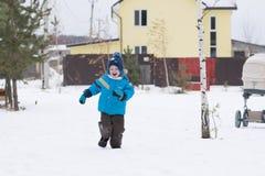 Happy boy running at a winter cottage village stock photos