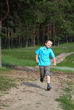 Happy boy runs near the forest Royalty Free Stock Photos