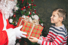 Happy boy and Santa Claus with big gift box! Merry Christmas!. Happy boy and  Claus with big gift box! Cristmas tree. Xmas and  Year holiday! Merry Royalty Free Stock Photos