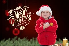Happy boy in santa hat holding christmas baubles Royalty Free Stock Photography