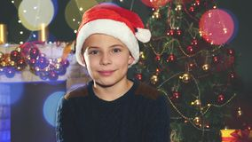 Happy boy in Santa hat near the decorated Christmas tree stock video