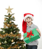 Happy boy in santa hat surprised by christmas present Royalty Free Stock Photos