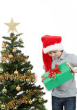Happy boy in santa hat surprised by christmas present Stock Photo