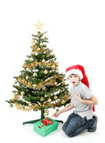 Happy boy in santa hat surprised by christmas present Stock Photos