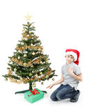 Happy boy in santa hat surprised by christmas present Royalty Free Stock Image