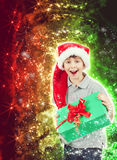 Happy boy in santa hat surprised by christmas present Royalty Free Stock Photo