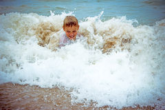 Happy boy at the sea lying in sand and waves Stock Photo