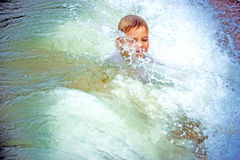 Happy boy at the sea lying in  sand and waves Stock Images