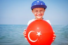 Happy boy on sea, Turkey. Smilling child with ballon of turkish flag. Holiday on sea beach.  Stock Image
