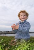 Happy Boy at Seaside. Happy Toddler clapping his hands. In the background the sea and a harbour Stock Image