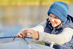 Happy boy setting up tent outdoors Stock Images