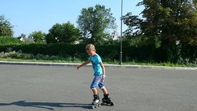 Happy boy of seven, rollerblading, a hot summer day. Slow motion stock video