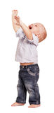 Happy boy in shirt, jeans his hands raised up isolated. Stock Photography