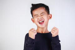 Happy Boy Shout with Joy of Victory. Success concept, portrait of happy young Asian boy showing enthusiastic winning gesture shout with joy of victory Royalty Free Stock Photography