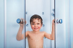 Happy boy in the shower cabin wet and smiling Stock Photo