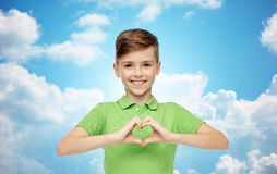 Happy boy showing heart hand sign over blue sky. Childhood, love, charity, health care and people concept - happy smiling boy in green polo t-shirt showing heart Stock Photos