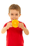 Happy boy showing orange slice Royalty Free Stock Photos