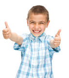 Happy boy is showing thumb up gesture. Using both hands, isolated over white Royalty Free Stock Photography