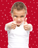 Happy boy is showing thumb up gesture. Using both hands, over red snowy background Stock Photography