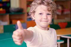 Happy boy showing thumbs up gesture on kindergarten background. Activities with children in kindergarten. Happy boy showing thumbs up gesture on kindergarten Royalty Free Stock Photography