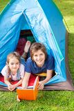 Happy Boy With Sister Reading Book In Tent Stock Photos