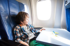 Happy boy sit in plane with toy model on table Royalty Free Stock Image