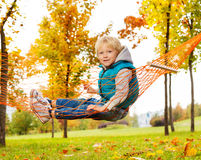 Happy boy sits on net of hammock in the park Stock Image