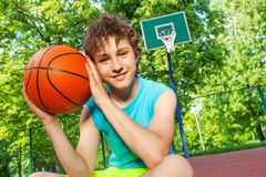 Happy boy sits on playground, holds ball near face Stock Photography