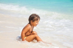 Happy boy sits on the sand beach with white waves Stock Image