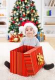 Happy boy sitting behind big present. Happy boy sitting behind big open Christmas present box Royalty Free Stock Photography