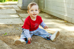 Happy boy is sitting on the damp ground Royalty Free Stock Photos