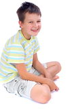 Happy boy sitting on floor. Happy boy sitting crossed legged on white floor. Background is white. Boy is wearing pastel colored t-shirt with horizontal stripes stock photography